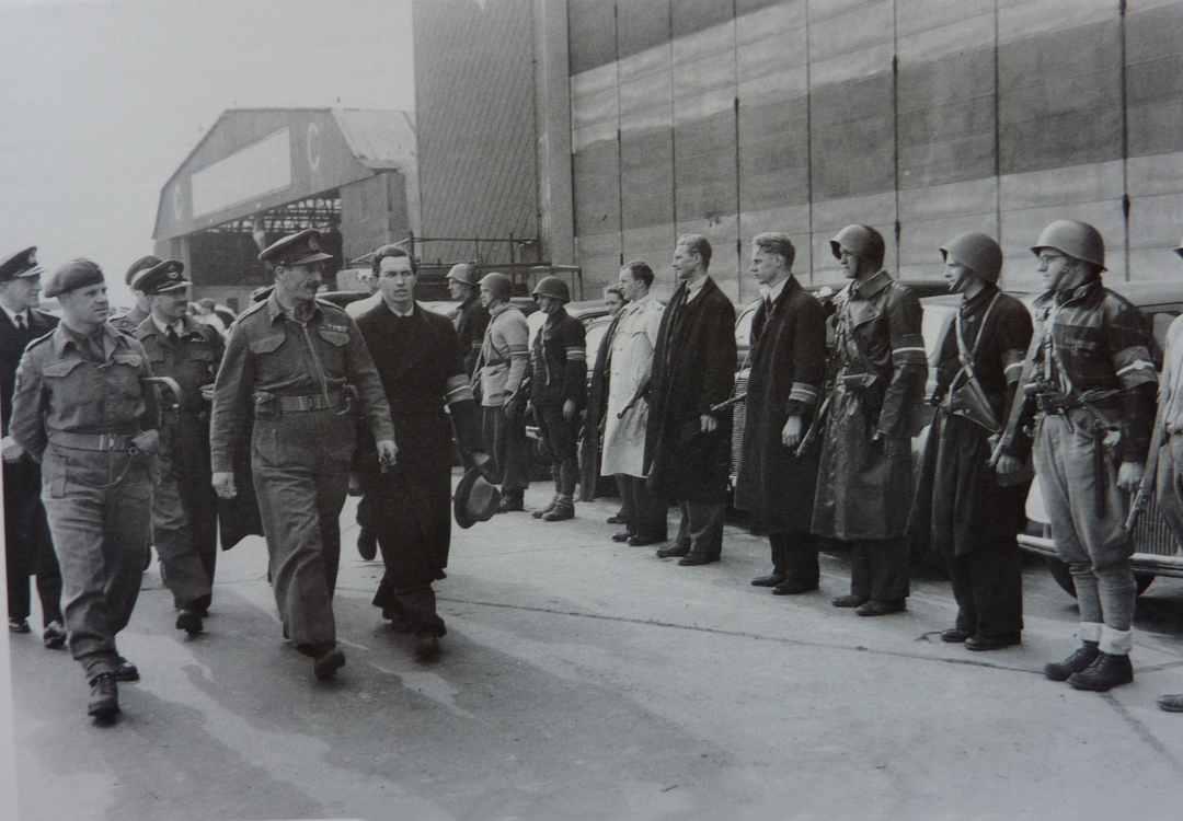 Ole Lippmann (med blød hat i venstre hånd) modtager den engelske general Dewing fra de allieredes hovedkvarter foran et æreskompagni af modstandsfolk 5 maj 1945. På dette tidspunkt var tanken om Det Udenrigspolitiske Selskab født. Det blev stiftet året efter.